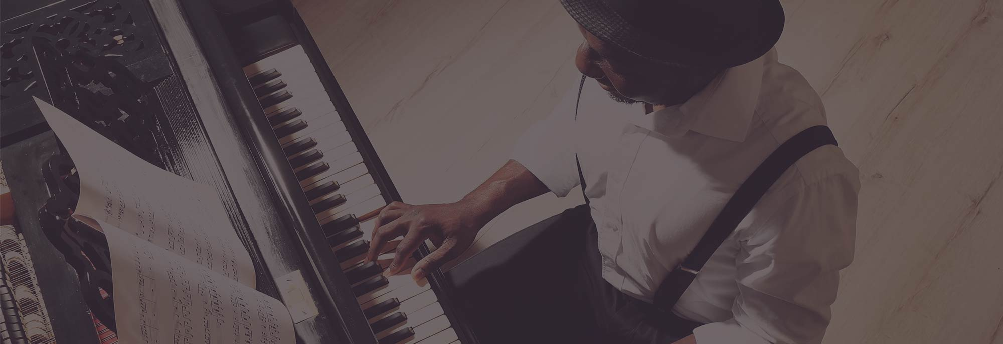 Man in suspenders playing piano