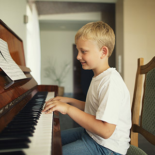 Boy playing upright piano