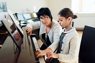 Woman teaching piano lessons